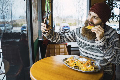 Hipster man taking selfie while eating tortilla chip with smart phone at cafe - CAVF56719