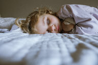 Cute girl with toy sleeping on bed at home - CAVF56749