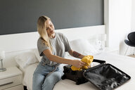 Smiling young woman sitting on bed with suitcase - VABF01844