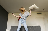 Carefree young woman jumping on couch at home - VABF01859