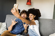 Happy couple sitting on couch taking a selfie - VABF01862