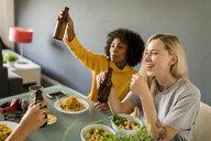 Happy girlfriends sitting at dining table raising beer bottles - VABF01868