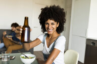 Portrait of smiling woman raising beer bottle at dining table - VABF01892