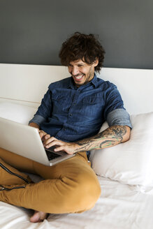 Happy tattooed man sitting on bed using laptop - VABF01934