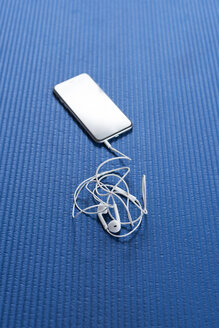 Smartphone and earphones on blue workout mat - SKAF00060