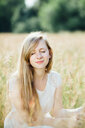 A beautiful young woman with long hair sitting in a field - INGF08014