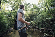 Back view of young man fishing in a forest - VPIF01159