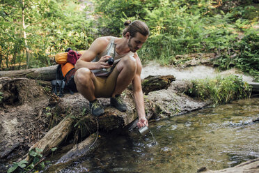 Young hiker scooping fresh water in a forest - VPIF01171