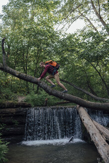 Young hiker with backpack crossing water on tree trunk in the forest - VPIF01177