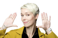 Portrait of smiling woman with short blond dyed hair in front of white background gesturing - FLLF00045