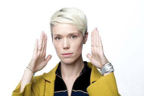 Portrait of woman with short blond dyed hair in front of white background gesturing - FLLF00048