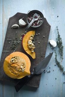 Sliced Hokkaido pumpkin and herbs on wooden board - ASF06262