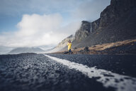 Iceland, woman walking on lane of country road - OCMF00119