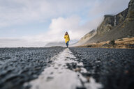 Iceland, woman walking on median strip of country road - OCMF00122