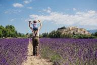 France, Grignan, back view of mother standing between lavender fields with little daughter on her shoulders - GEMF02603