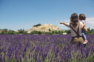 France, Grignan, back view of mother and little daughter standing together in lavender field looking at village - GEMF02621