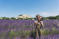 France, Grignan, happy mother carrying her little daughter through lavender field - GEMF02627