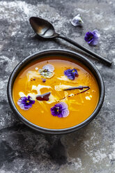 Bowl of creamed pumpkin soup garnished with edible flowers - SARF03991