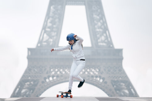 Full length of young woman skateboarding against Eiffel tower - CAVF56763