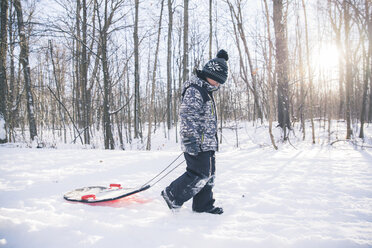 Side view of boy with sled walking on snowy field against bare trees - CAVF56772