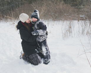 Cheerful mother and son on snowy field - CAVF56775