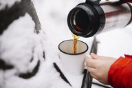 Cropped hands of woman pouring black coffee from insulated drink container into mug on snow - CAVF56790