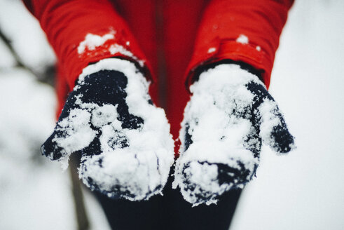 Midsection of woman wearing gloves while holding snow during winter - CAVF56793