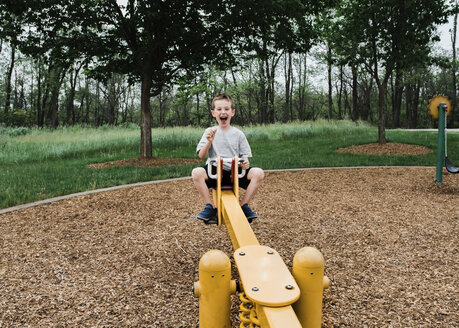 Portrait of happy boy playing on seesaw at park - CAVF56808