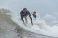 Portrait of friends surfing on sea against cloudy sky - CAVF56817