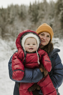Portrait of mother carrying daughter while standing in forest during winter - CAVF56850