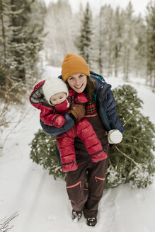 Portrait of smiling mother carrying daughter while pulling pine tree in forest during winter - CAVF56853