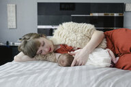 Mother breastfeeding newborn daughter while lying on bed at home - CAVF56880