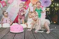 Baby girls with birthday cakes on floorboard - CAVF56898