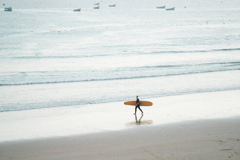 Full length of man carrying surfboard while walking on shore at beach - CAVF56934