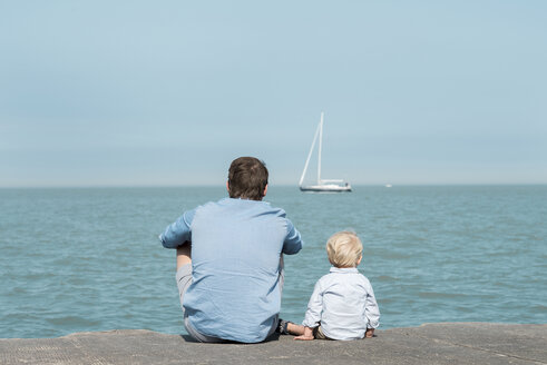 Rear view of father with son sitting at beach against blue sky during sunny day - CAVF56949