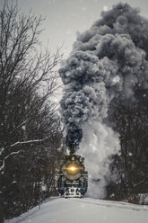 Train moving on snow covered railroad track amidst bare trees against sky - CAVF56976