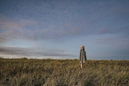 Girl standing on grassy field against sky during sunset - CAVF56991