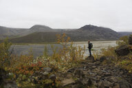 Full length of hiker looking at view while standing on rock at riverbank against mountains - CAVF57021
