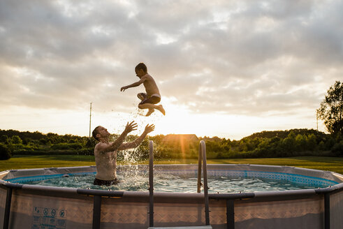 Father catching son while swimming in wading pool against cloudy sky at backyard during sunset - CAVF57033