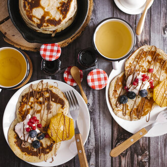 Overhead view of pancakes with preserves and fruits on wooden table - CAVF57051