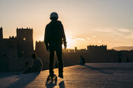 Rear view of man skateboarding against sky during sunset - CAVF57060