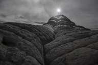 Low angle view of man with illuminated flashlight standing on Marble Canyon against sky during night - CAVF57093