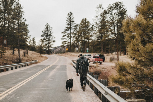 Rear view of male hiker with dog walking on road - CAVF57144