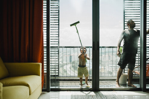 Father and son cleaning windows in balcony seen through glass - CAVF57159
