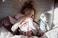 Overhead portrait of cute girl covering eye with textile while lying on bed at home - CAVF57183