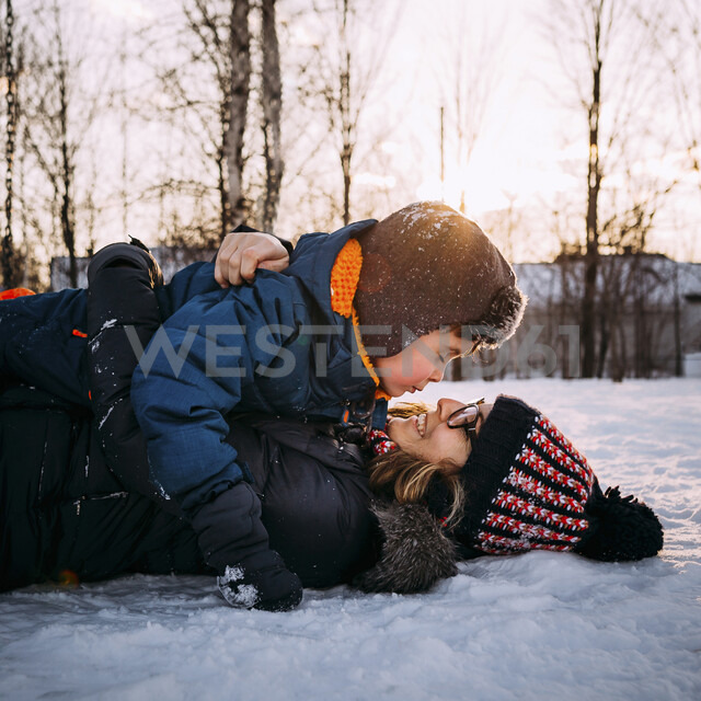 Happy mother with son lying on snow covered field against sky during sunset - CAVF57201 - Cavan Images/Westend61
