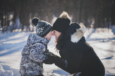 Playful mother and son rubbing noses on snowy field - CAVF57237