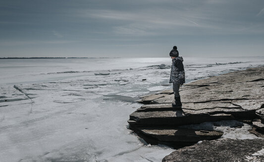 Side view of boy standing by frozen sea against sky - CAVF57240