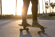 Low section of woman standing on skateboard during sunset - CAVF57243