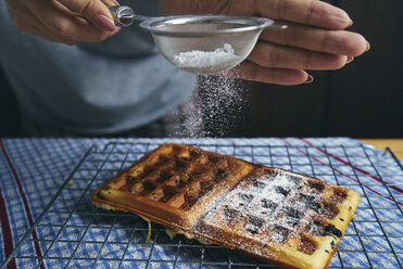 Midsection of woman sprinkling powdered sugar on waffle at table - CAVF57285
